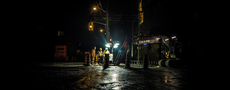 Crew of public works staff working on roadway at night