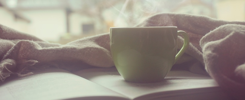 Coffee cup and book on table